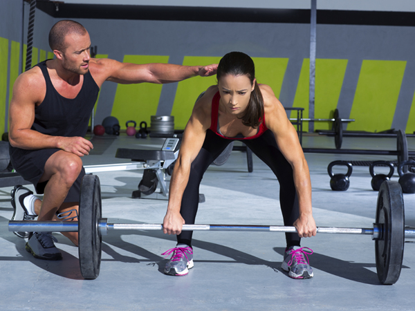 gym personal trainer man with weight lifting bar woman workout in crossfit exercise